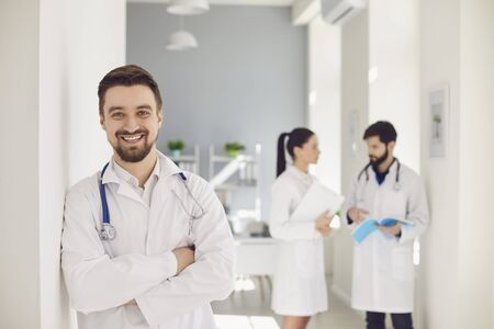 A practicing doctor with a stethoscope smiles against the background of a doctor at the clinic. Successful positive doctor therapist looking at the camera while standing in a hospital. Stock fotó