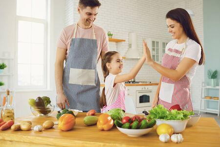 Happy family with kid preparing fresh vegetables on the table in the kitchen. Healthy eating. Parents with daughter cut a salad with a knife in the kitchen in the house. Archivio Fotografico