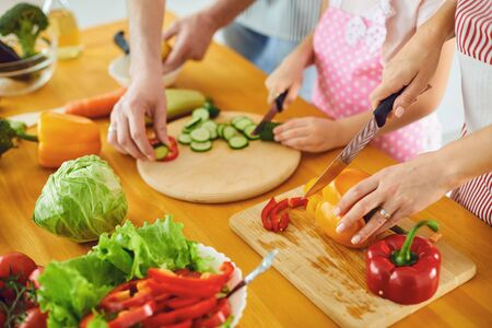 Faceless. Family hands prepare fresh vegetables salad on the table in the kitchen. Mother's hands cut vegetables with a knife. Healthy eating Foto de archivo