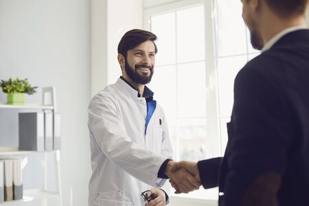 Handshake. Practicing doctor and patient shaking hands smiling at the clinic. Successful treatment in the hospital. Satisfied patient. Health. Stock fotó
