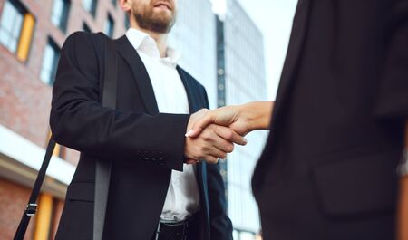 Handshake business. Businessman and business woman make handshakes while standing outdoors at a business building. Success concept deal contract project bank. 版權商用圖片