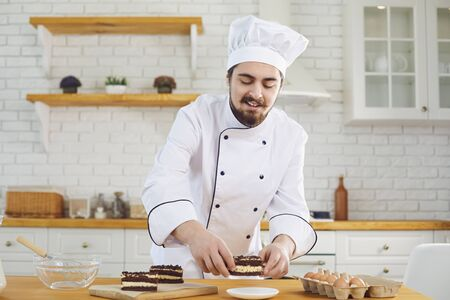 A male pastry chef works decorating a cake on a kitchen bakery.