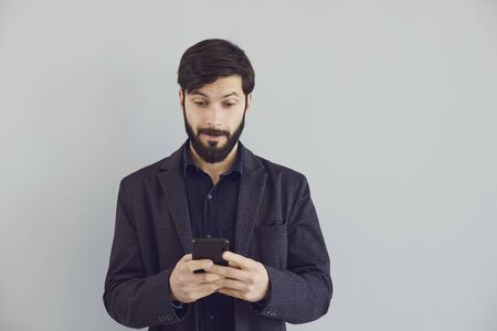Positive bearded guy in a jacket is typing text in a mobile smiling with on a gray background. Portrait of a young businessman guy with a smartphone 版權商用圖片