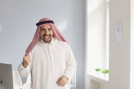 Arab man businessman smiling stands in a white office.