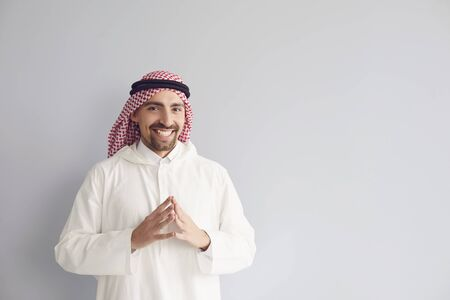 Arab male businessman smiling portrait standing on a gray background.