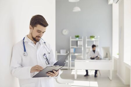 A male doctor with a stethoscope reads a clipboard while standing in a clinic. Practicing physician therapist on the background of a medical office.