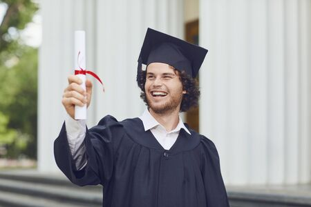 A young man graduate with a scroll in his hands is smiling against the background of university graduates. Graduation.University gesture and people concept.