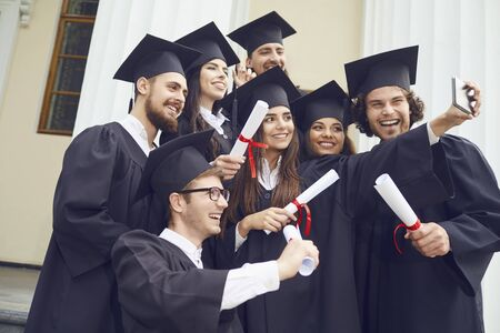 Students graduates are photographed on the phone at the university college. Graduation.University gesture and people concept.
