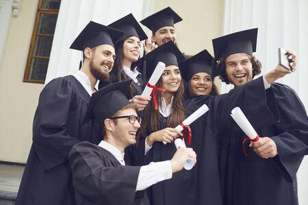 Absolventen der Studenten werden am Telefon an der Hochschule fotografiert. Graduation.University-Geste und People-Konzept.