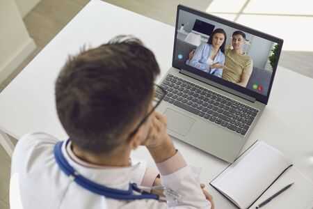 Doctor medical online call.Shoulder view doctor therapist psychologist speaks with couple video chat using a laptop in a clinic office. Telemedicine concept. Medical insurance for the treatment of patients. Archivio Fotografico