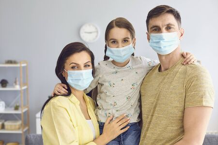 Family in medical masks on the face looks at the camera while standing in the room at home. The concept of quarantine protection self-isolation virus pandemic coronavirus.