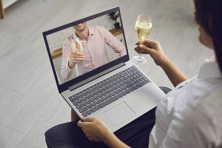 オンライン日付。自宅でロマンチックな設定でビデオ通話のラップトップを使用して日付距離にワインのグラスと愛するカップル。聖バレンタインデー。