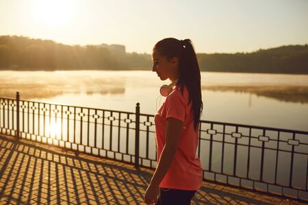 A young girl in training warm up at sunrise by the lake in the park in the summer in autumn.