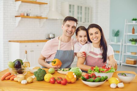 Happy family with daughter in the kitchen with vegetables smiling look at the camera. Parents with daughter cut a salad with a knife in the kitchen in the house. Stockfoto