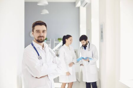 A male practicing doctor with a stethoscope against the background of a doctor at the clinic. Successful positive doctor therapist looking at the camera while standing in a hospital.