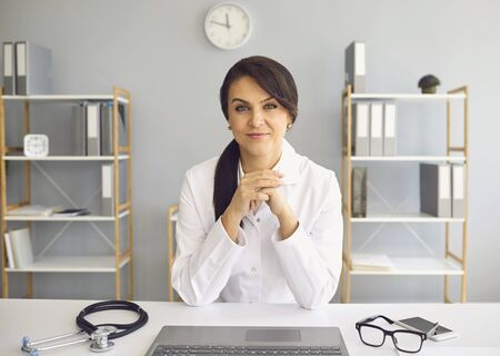Female practicing doctor looking at the camera while sitting at a table in a clinic office. Health care worker. Stock fotó