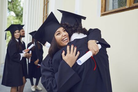 Graduates with diplomas in their hands hugging laugh at the background of the education, Graduation.University gesture and people concept.
