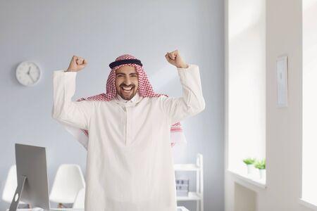 Der positive lächelnde arabische Geschäftsmann jubelt und hob seine Hände in einem hellen hellen Raum des weißen Büros.
