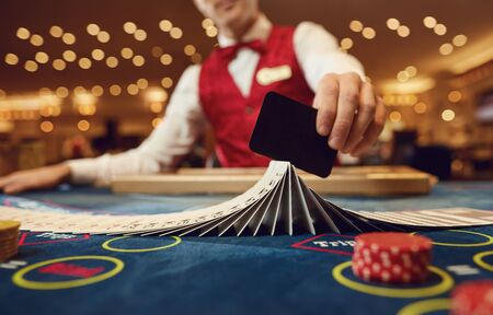 The croupier holds poker cards in his hands at a table in a casino. Stock Photo