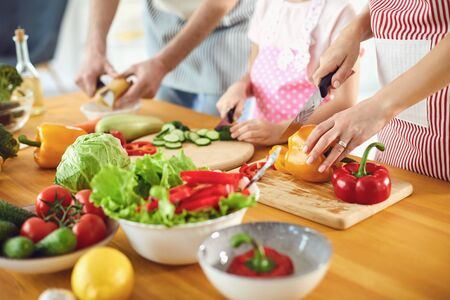 Family cooks fresh vegetables on the table in the kitchen. Hands of mother father and daughter with a knife are preparing a vitamin salad. No faces.