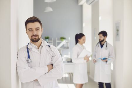 A male practicing doctor with a stethoscope against the background of a doctor at the clinic. Successful positive doctor therapist looking at the camera while standing in a hospital. Stock fotó