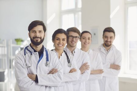A group of confident practicing doctors in white coats are smiling against the backdrop of the clinic. Doctors team in a medical hospital.