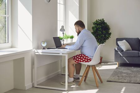 Online work at home. Funny fat businessman in red shorts works communicates using laptop sitting at the table at the workplace at home office in the room.