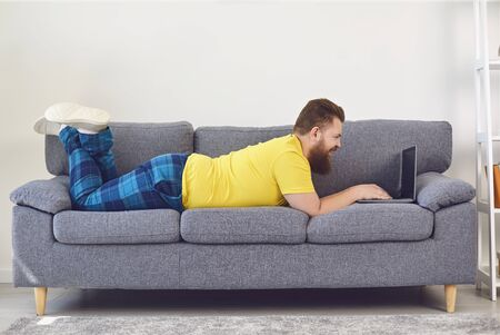 Funny fat man working online shopping shrpping watching a video at home in the room. Work online at home office. Standard-Bild