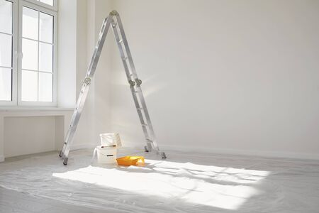 Concept painting work repair painting. Ladder paint cans in a white room for repair. Stockfoto