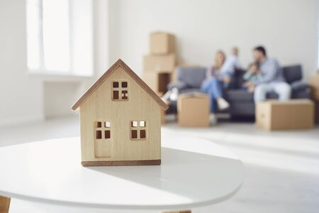 The concept of moving a new home housing apartment construction mortgage rental. Layout of the wooden house on the family background in new building apartment. Foto de archivo