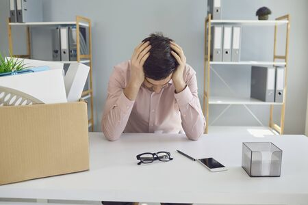 Unemployment. Dismissal. Dismissed businessman is upset with a cardboard box holding his head in his hands while sitting at a table in the company office. Stress failure Depression crisis problems without work. Фото со стока