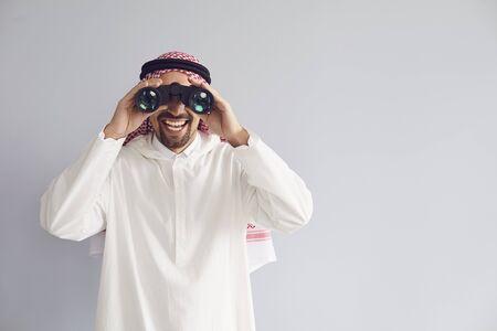 Arab man looking through binoculars smiling on a gray background. Arab businessman searching is watching. Standard-Bild