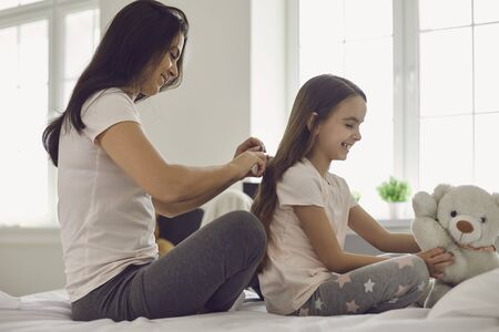 Mother makes hairstyle to girl child sitting on bed in bedroom. Mom is combing a comb daughter in the room. Parents care.