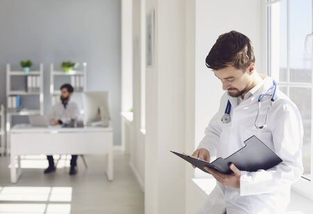 A male confident doctor with a stethoscope reading a clipboard while standing in a clinic. Practicing physician therapist on the background of a medical office. Stock fotó