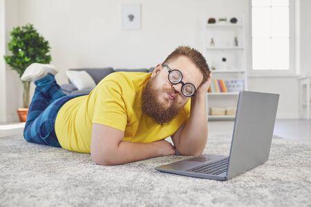 オンラインデートチャットビデオチャット通話。自宅の部屋でインターネットビデオ通話チャットアプリケーションを介してオンラインデートでラップトップで床に横たわっている愚か者のメガネで面白い太った男。 写真素材