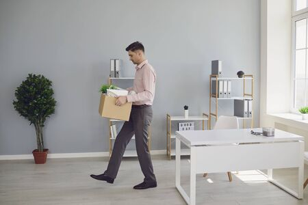 Unemployment. Dismissal. An unemployed man with a box is walking out of the office in search of a new job. Stress failure Depression crisis problems without work.