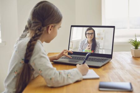 Online education of children. Girl schoolgirl teaches a lesson online using a laptop video chat call conference with a teacher sitting at a table at home. Фото со стока