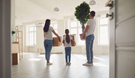 Familia sonriente se ríe mientras está de pie en una nueva casa soleada. Vista trasera. El concepto de mudanza inmobiliaria nueva casa de apartamentos mudanza casa compra venta propiedad alquiler habitación inversión. Foto de archivo