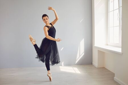 Ballerina in black clothes posing in a bright class studio with windows. Woman dancer dancing in a sunny room.