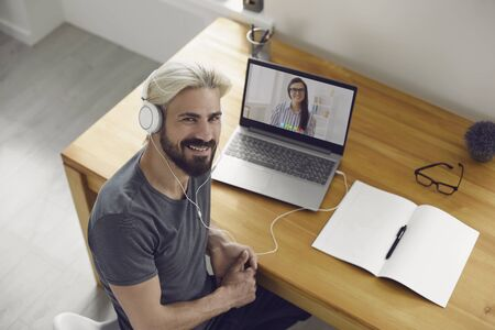 Education learning study online video call chat. Male student hipster smiling is studying an online lesson with a teacher using a laptop webcam application at home. 版權商用圖片
