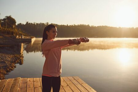 Workout exercises sport health by the lake in the morning.Girl holding dumbbell with her hands during a workout in the park in the morning at sunrise. Stock Photo