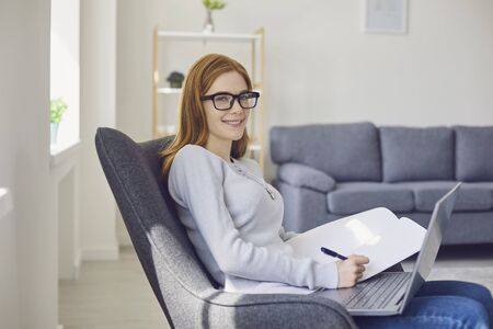 Learning online education. Red-haired girl in glasses studying using a laptop video call chat web camera watching video course college university sitting in a chair at home. Distance learning using the video lesson chat application.