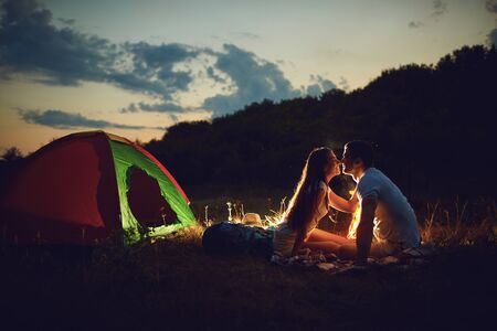 A young couple is cooking bread on a fire at romantic night by the tent. Imagens