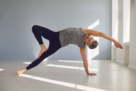 Yoga man. A man in sportswear is practicing yoga balance on the floor in a gray room. The concept of an active lifestyle of sports life sports yoga pilates meditation relaxation relaxation gym.