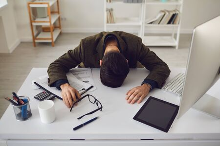 Businessman in a jacket tired exhausted with stress problems lying at the workplace in the office. 版權商用圖片