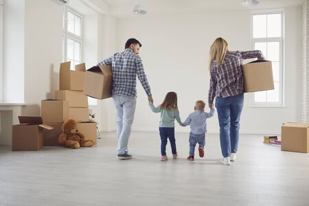 Happy family with children moving with boxes in a new apartment house. Relocation concept new house apartment rental housing.