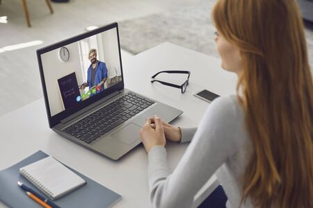 Online home lecture training. Student girl listening to teacher video chat call in laptop while sitting at table in room at home. Education training university college distance online internet concept.