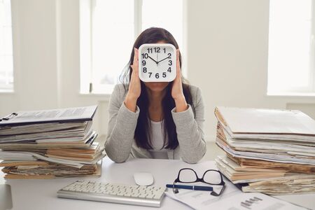 Business woman holding an alarm clock in front of her face while sitting at a table in the office.