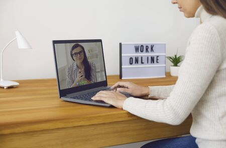 Online work at home. A woman works at a table in the workplace using a laptop she speaks with a partner through the video call chat application in the living room at home. Remote work at home.