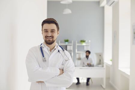 A male doctor cross arms with a stethoscope smiling while standing in a clinic. Practicing physician therapist on the background of a medical office. Stock fotó